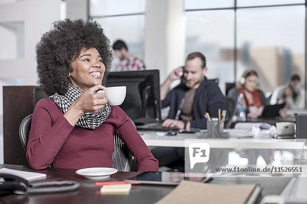 Lächelnde Frau am Schreibtisch im Büro beim Kaffeetrinken