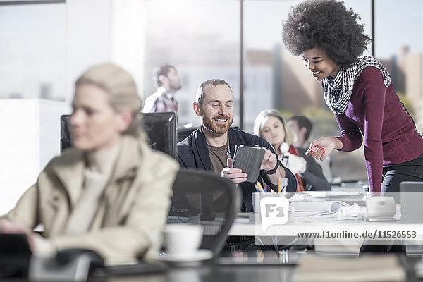 Lächelnder Mann am Schreibtisch im Büro zeigt dem Kollegen digitales Tablett