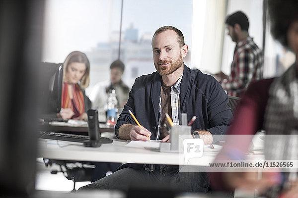 Porträt eines lächelnden Mannes am Schreibtisch im Büro umgeben von Mitarbeitern