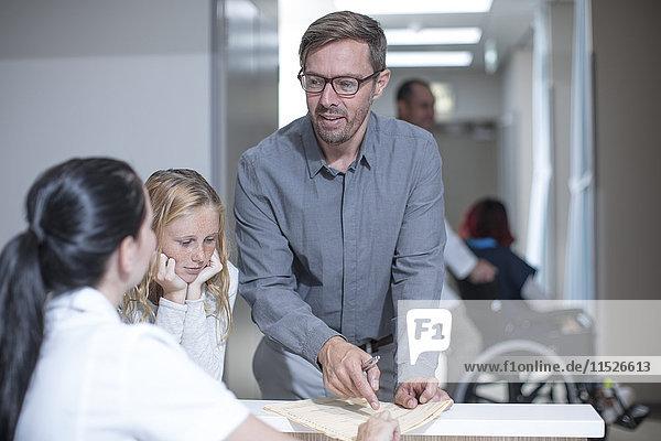 Vater und Tochter stehen an der Rezeption im Krankenhaus
