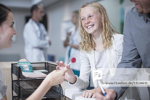 Krankes Mädchen bekommt Lollipop von der Empfangsdame in Hosptal