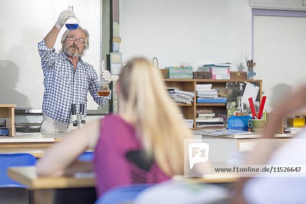 Naturwissenschaftslehrerin in der Klasse mit Fläschchen