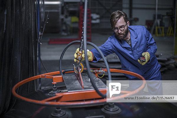Fabrikarbeiter beim Anbringen von Industriehaken aus Stahl