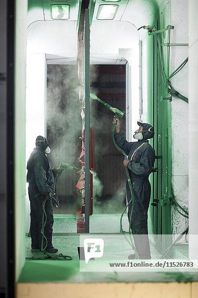 Lackierer beim Spritzen von Stahlteilen in der Spritzkabine einer Fabrik