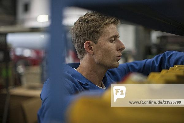 Fabrikarbeiter in der LKW-Fertigung auf der Suche nach Werkzeugen