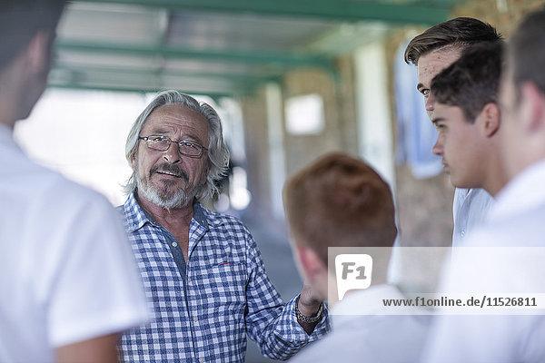 Lehrer im Gespräch mit Schülern auf dem Schulflur