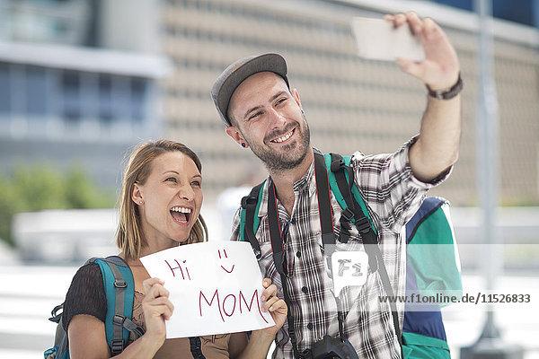Junges Reisepaar beim Fotografieren mit Schild'Hallo Mama