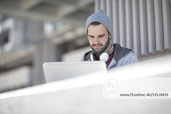 Junger Mann mit Laptop im Freien