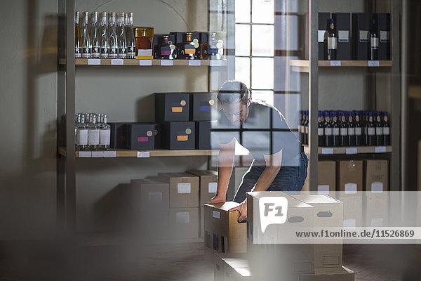 Mann beim Verpacken von Weinflaschen im Geschäft