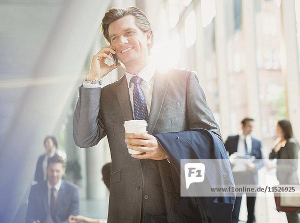 Lächelnder Geschäftsmann mit Kaffee am Handy in der Bürolobby