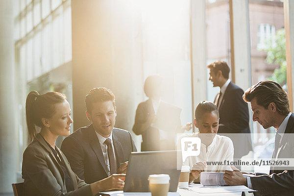 Geschäftsleute  die am Laptop arbeiten und den Papierkram im Meeting überprüfen