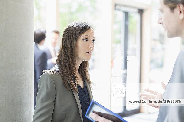 Seriöse Geschäftsfrau hört dem Geschäftsmann mit digitalem Tablett in der Bürolobby zu.