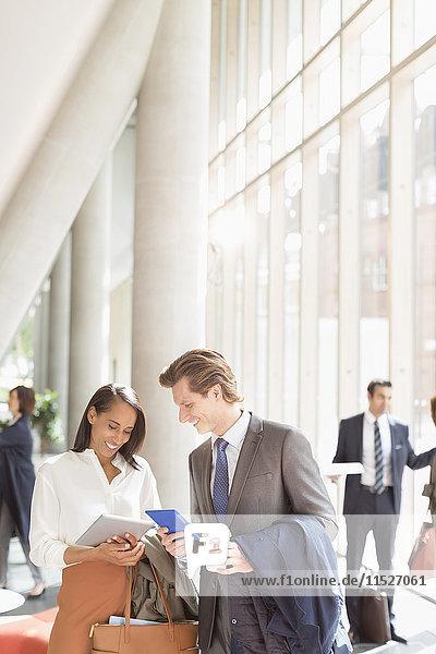 Geschäftsleute mit digitalen Tabletts sprechen in der sonnigen Bürolobby