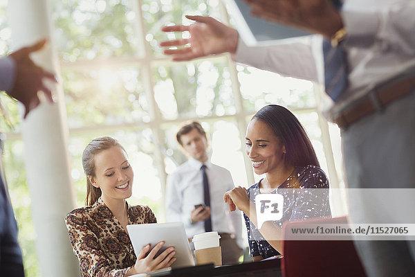 Geschäftsfrauen nutzen digitales Tablett im Büromeeting