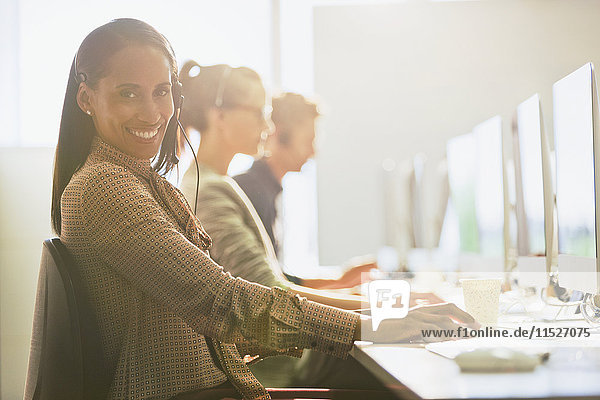 Portrait lächelnde Telemarketerin mit Headset am Computer im sonnigen Büro