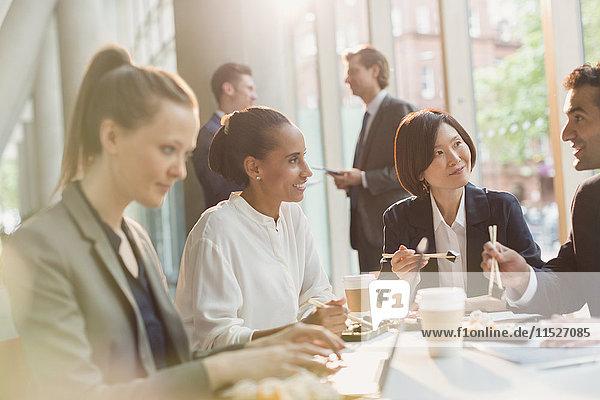 Geschäftsleute beim Sushi-Lunch mit Essstäbchen im Konferenzzimmer