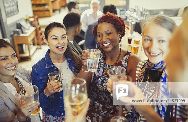 Frauenfreunde toasten Wein und Biergläser an der Bar