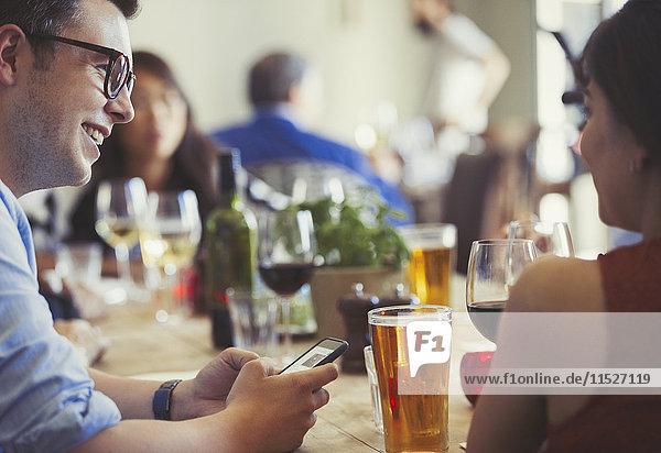 Paar mit Handy sprechen und Bier und Wein am Restauranttisch trinken