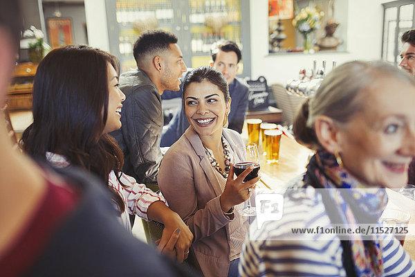 Lächelnde Frauenfreunde beim Reden und Weintrinken in der Bar