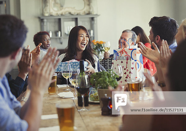 Freunde klatschen für eine glückliche Frau  die am Restauranttisch Geburtstag feiert.