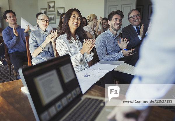 Lächelnde Geschäftsleute klatschen für den Geschäftsmann  der die Konferenz am Laptop leitet.