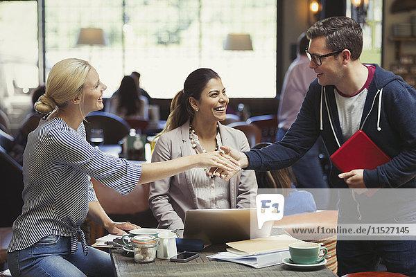 Kreative Geschäftsleute beim Begrüßen  Händeschütteln im Cafe