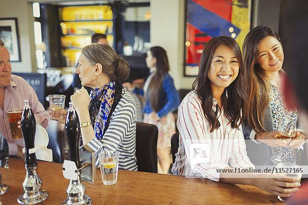 Frauen lächeln dem Barkeeper zu und trinken an der Bar.