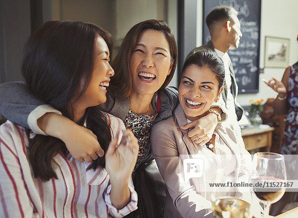 Enthusiastische  lächelnde Frauen  die sich in der Bar umarmen und trinken.