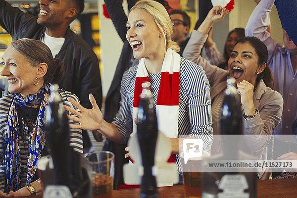 Begeisterte Sportfans beim Jubeln und Zuschauen in der Bar