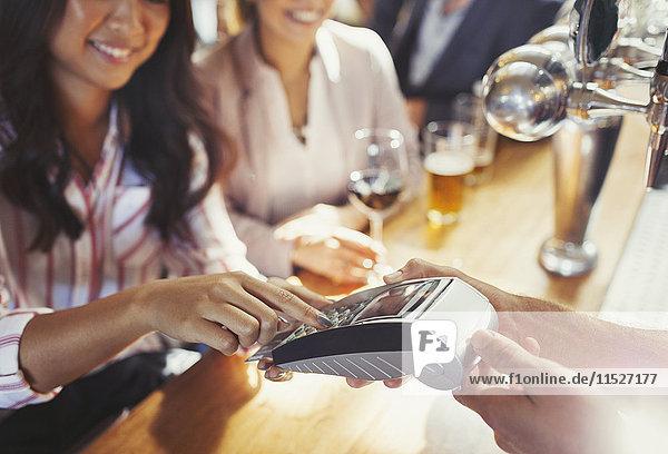 Bezahlende Barkeeperin mit Kreditkarte an der Bar