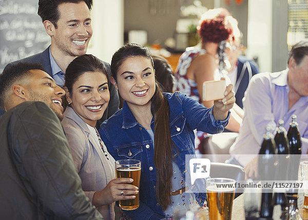 Verspielte Freunde trinken Bier und nehmen Selfie mit Fotohandy an der Bar.