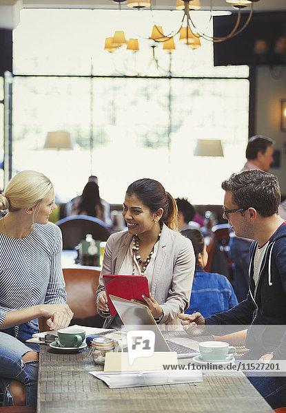 Kreative Geschäftsleute treffen sich mit digitalem Tablett und Laptop im Cafe