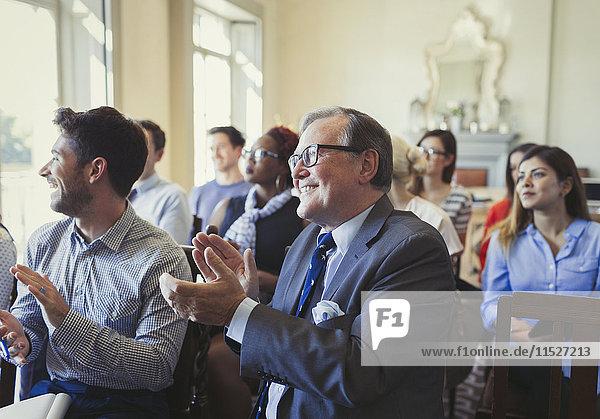 Lächelnde Geschäftsleute klatschen im Publikum der Business-Konferenz