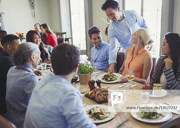 Kellner serviert Essen an Freunde  die am Restauranttisch speisen.