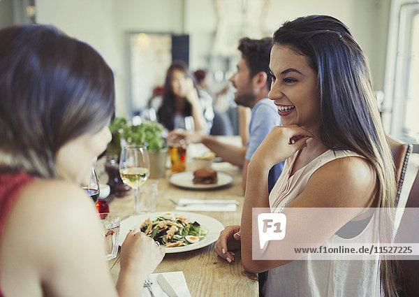 Lächelnde Freundinnen beim Essen und Reden am Restauranttisch