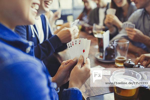 Frau hält Asse  spielt Poker und trinkt Bier mit Freunden am Tisch in der Bar.