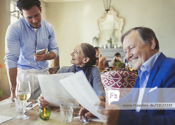 Kellner  der die Bestellung vom Seniorenpaar entgegennimmt  mit Menüs am Restauranttisch.