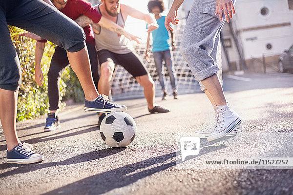 Freunde spielen Fußball in der Sommerstraße