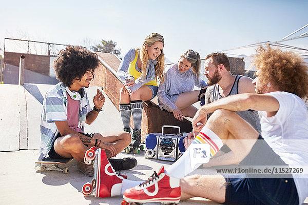Freunde in Rollschuhen beim Musikhören im sonnigen Skatepark