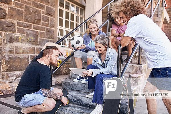 Freunde  die mit einem digitalen Tablett auf einer städtischen Treppe rumhängen.