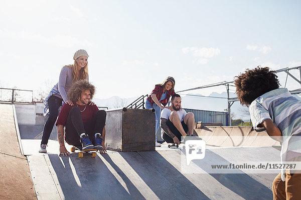 Freunde schieben sich auf Skateboards im sonnigen Skatepark.