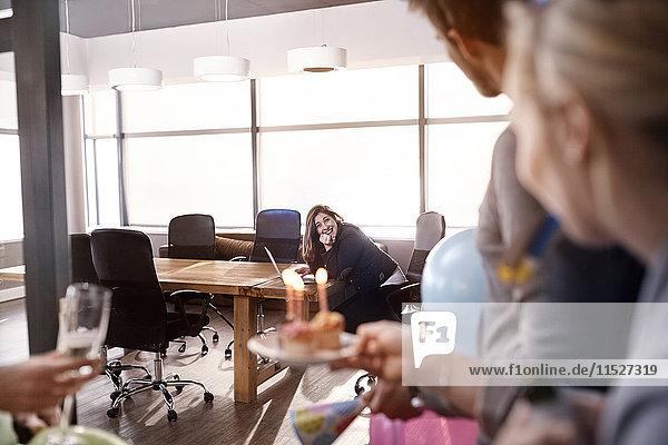 Geschäftsleute überraschen Geschäftsfrau mit Geburtstagskuchen im Konferenzraum