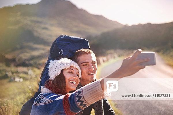 Junges Paar mit Rucksäcken beim Wandern mit Fotohandy auf sonniger  abgelegener Straße