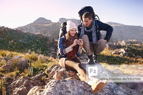 Junges Paar mit Rucksäcken beim Wandern  das sich mit dem Smartphone auf dem Felsen ausruht.