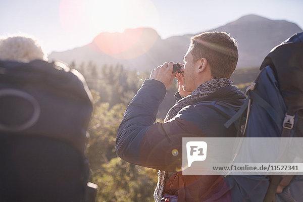 Junger Mann mit Rucksackwanderung mit Fernglas im Sonnenfeld