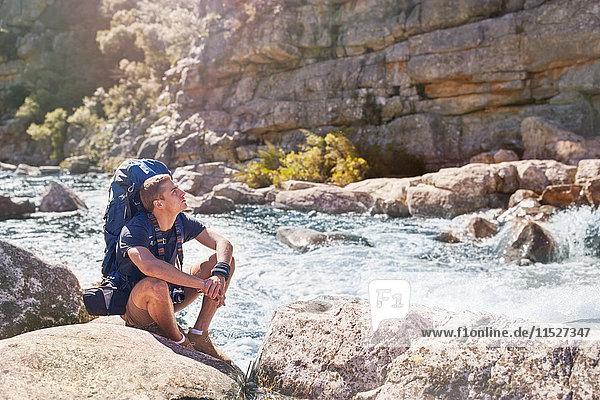 Junger Mann mit Rucksackwanderung  Rast am sonnigen  zerklüfteten Bach