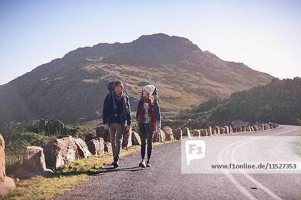 Junges Paar mit Rucksäcken auf abgelegener  sonniger Straße