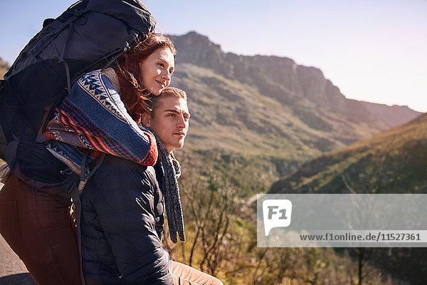Zärtliches junges Paar mit Rucksackwandern  Pause in sonniger Landschaft
