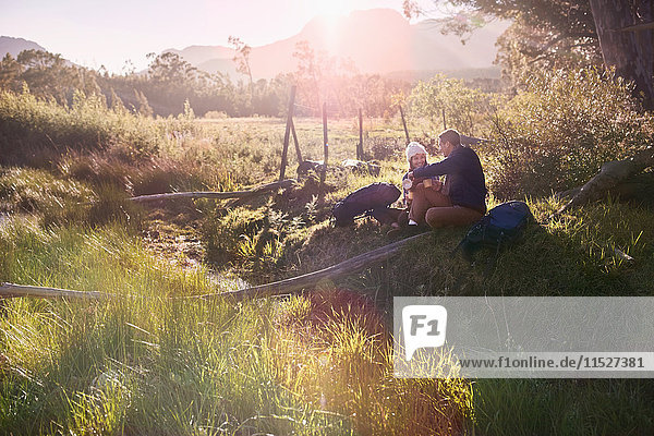 Junges Paar mit Rucksackwanderung  Erholung im sonnigen abgelegenen Feld