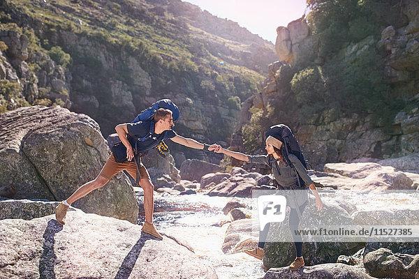 Junger Mann hilft Freundin beim Wandern  überquert sonnige Felsen im Bach